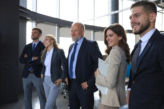 Retrato de grupo de uma equipe profissional de negócios, olhando com confiança para a câmera.