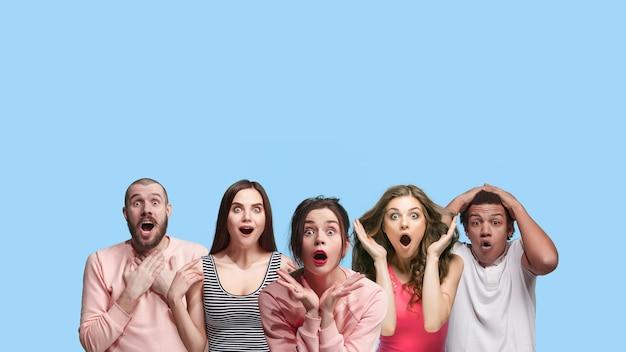 Retrato de grupo multiétnico de jovens isolados em fundo azul studio, panfleto, colagem. conceito de emoções humanas, expressão facial, vendas, publicidade. chocado, espantado, pensado como louco.