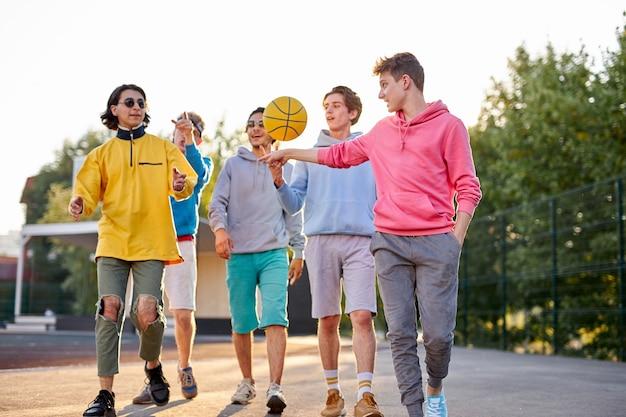Retrato de grupo positivo de jovens veio jogar basquete