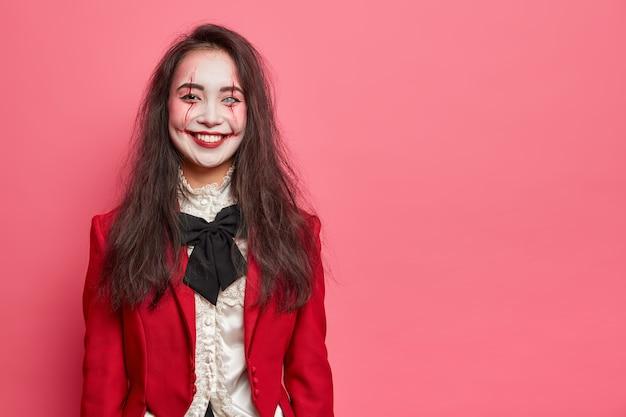 Retrato de halloween de uma mulher alegre com maquiagem profissional estando de bom humor e vestindo uma fantasia e fazendo poses de festa de máscaras contra uma parede rosada com espaço em branco para sua informação