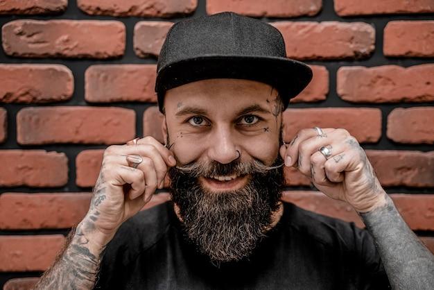 Retrato de hipster bonito à moda antiga em t-shirt e boné, tocando sua barba e sorrindo. em um fundo de tijolo.