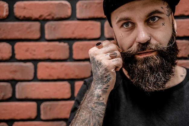 Retrato de hipster bonito à moda antiga em t-shirt e boné, tocando sua barba. em um fundo de tijolo.