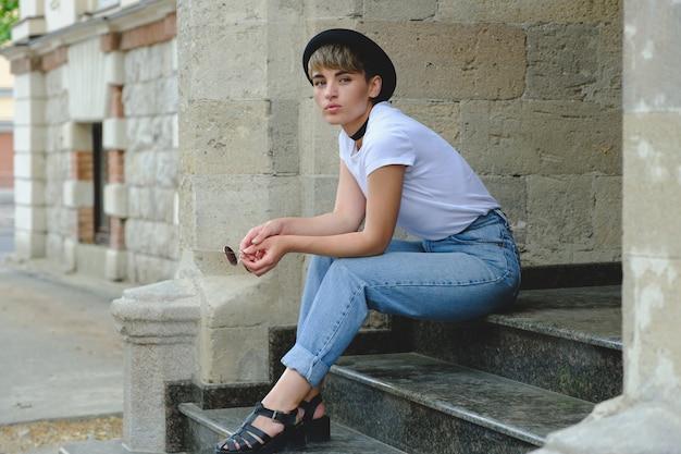Retrato de hipster feminino com maquiagem natural e cabelo curto, aproveitando o tempo de lazer ao ar livre