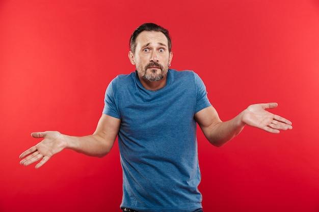 Retrato de homem adulto caucasiano, olhando para a câmera, expressando mal-entendidos com vomitando as mãos, isoladas sobre fundo vermelho