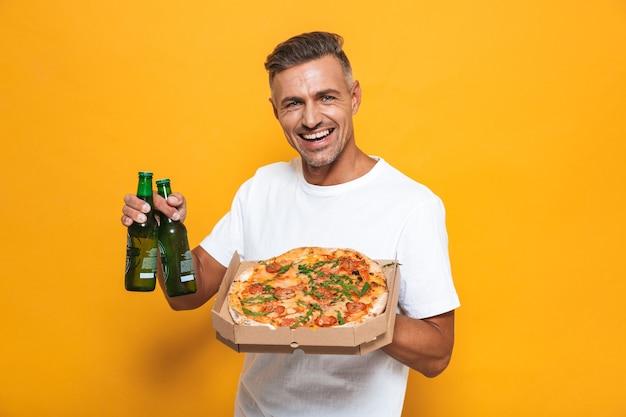 Retrato de homem adulto de 30 anos em uma camiseta branca bebendo cerveja e comendo pizza em pé isolado no amarelo