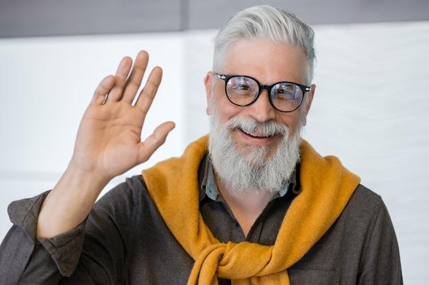 Retrato de homem adulto de cabelos grisalhos bonito de um homem de negócios em uma camisa escura e suéter amarelo