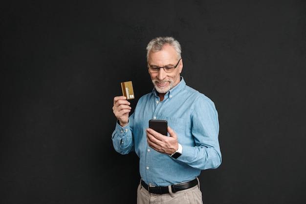 Retrato de homem adulto dos anos 60, com cabelos grisalhos e barba, pagar com cartão de crédito enquanto fazia compras através da internet usando o celular, isolado sobre a parede preta