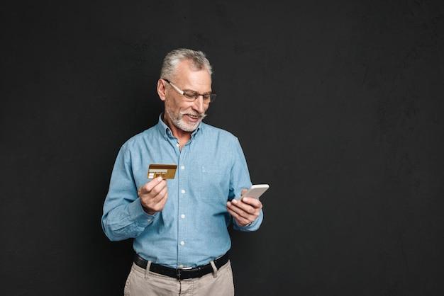 Retrato de homem adulto dos anos 60, com cabelos grisalhos e barba, pagar com cartão de crédito enquanto fazia compras on-line usando a internet e telefone celular, isolado sobre a parede preta