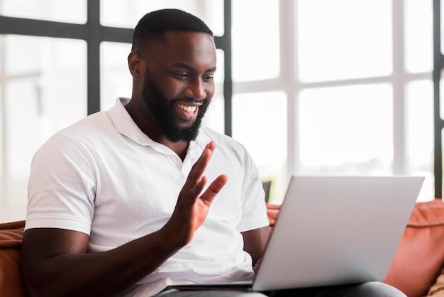Retrato de homem adulto, fazendo videochamada com amigo