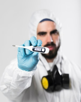 Retrato de homem adulto, segurando um termômetro