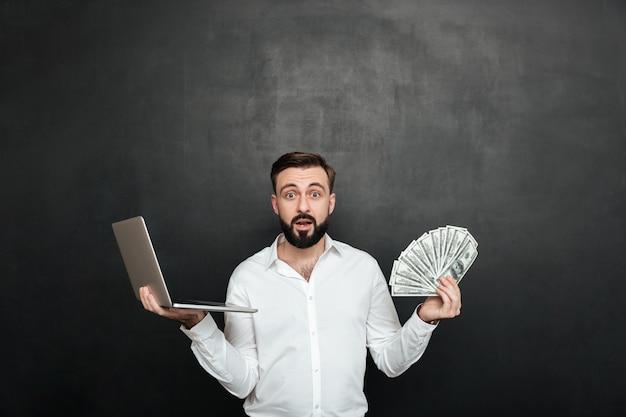 Retrato de homem adulto surpreso na camisa branca, segurando o leque de notas de dólar de dinheiro e caderno de prata em ambas as mãos sobre cinza escuro
