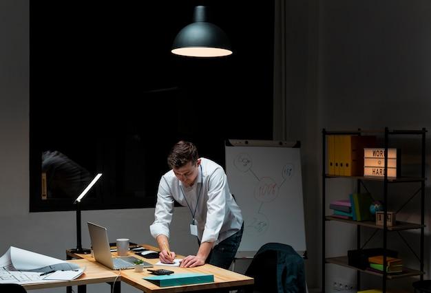 Retrato de homem adulto, trabalhando em casa à noite
