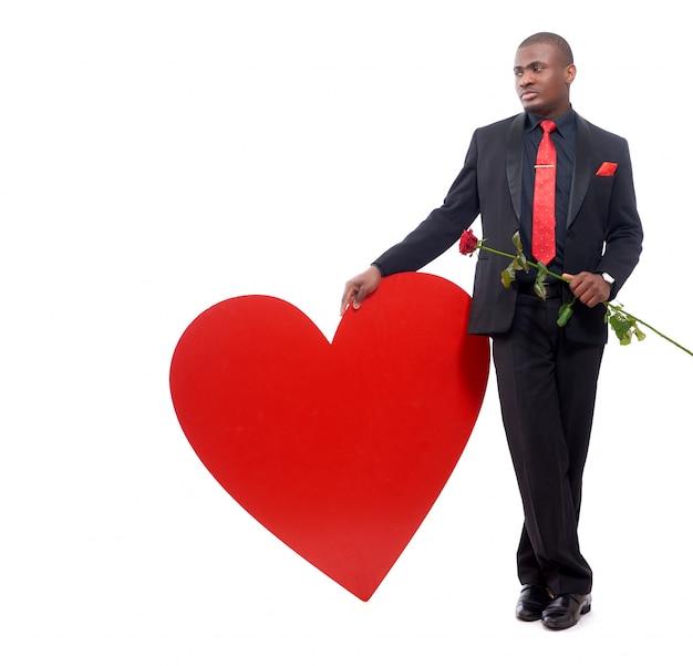 Retrato de homem africano bonito, inclinando-se de grande coração vermelho decorado e segurando a rosa vermelha