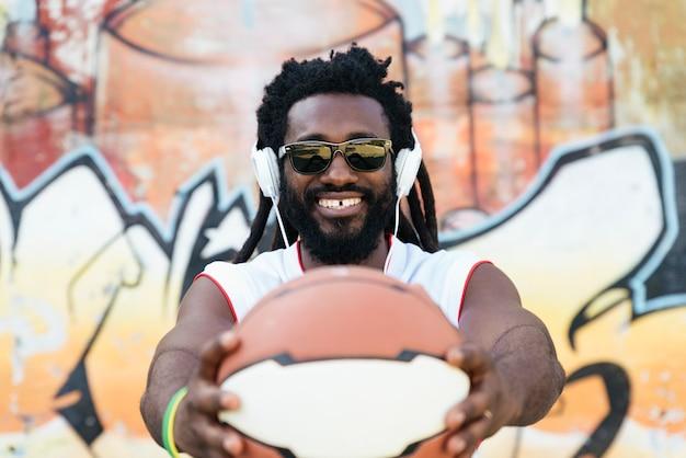 Retrato de homem africano com roupas esportivas casuais e bola de basquete.