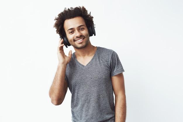 Retrato de homem africano em fones de ouvido sem fio, ouvindo o serviço de streaming de música e curtindo a batida