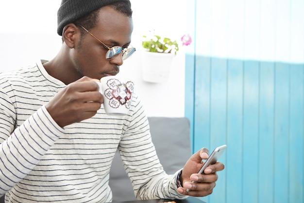 Retrato de homem africano em roupas elegantes, segurando a caneca, bebendo café fresco, navegando na internet e verificando o feed de notícias nas mídias sociais, usando o celular durante o café da manhã no café com assentos aconchegantes