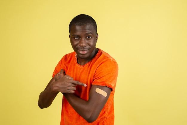 Retrato de homem africano isolado na parede amarela do estúdio