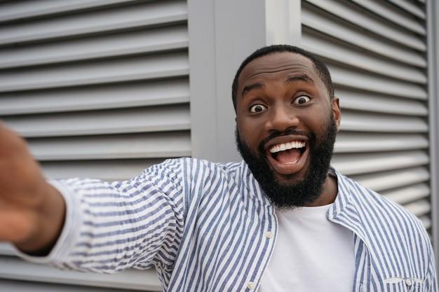 Retrato de homem afro-americano animado, tomando selfie pelo celular. influenciador de blogueiro emocional gravando vídeo ao ar livre