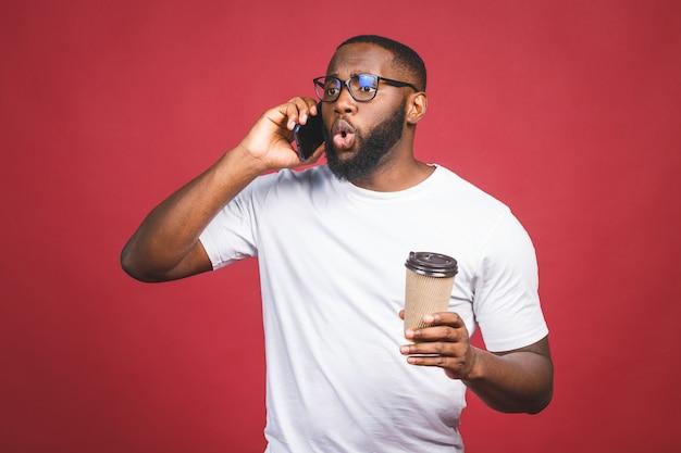 Retrato de homem afro-americano bonito surpreso com telefone móvel e tirar a xícara de café. isolado sobre o fundo vermelho.