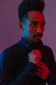 Retrato de homem afro-americano casual em roupas esportivas posando no isolado sobre a parede violeta.