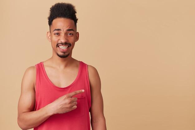 Retrato de homem afro-americano com barba e penteado afro. usando um top vermelho. aperte os olhos e sorria. apontando para a direita no espaço da cópia, isolado sobre a parede bege