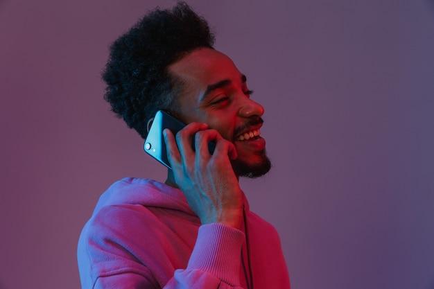 Retrato de homem afro-americano com barba por fazer, com capuz colorido, falando no celular isolado sobre a parede violeta
