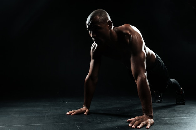 Retrato de homem afro-americano de esportes, fazendo exercícios de flexão