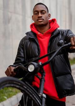 Retrato de homem afro-americano e sua bicicleta