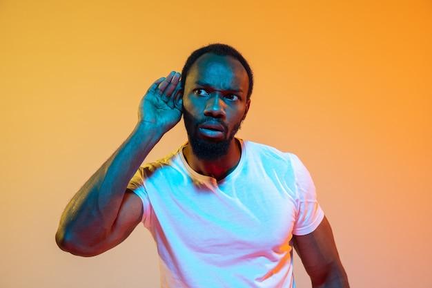 Retrato de homem afro-americano isolado em laranja gradiente em luz de néon