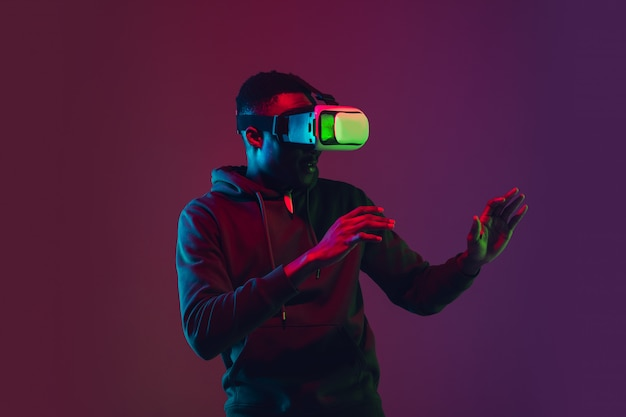 Retrato de homem afro-americano isolado na parede gradiente na luz de neon