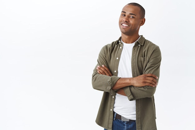Retrato de homem afro-americano profissional e inteligente, de pé com as mãos cruzadas no peito, pose confiante