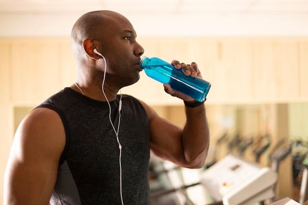 Retrato de homem afro-americano se hidratando durante a prática de esportes. foco seletivo.