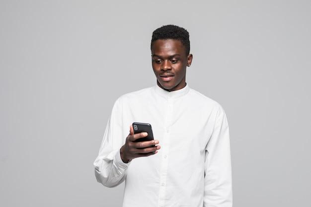 Retrato de homem afro bonito, enviando e recebendo mensagens para seu amante, isolado no fundo cinza