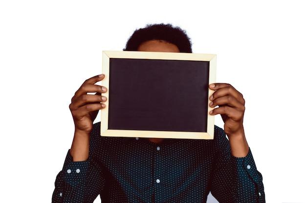 Retrato de homem afro, segurando uma lousa vazia no estúdio. conceito de publicidade. parede branca isolada