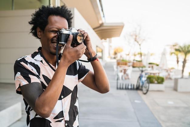 Retrato de homem afro tirando fotos com a câmera enquanto caminha ao ar livre na rua