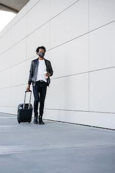 Retrato de homem afro-turista carregando mala e segurando uma xícara de café enquanto caminha ao ar livre na rua. conceito de turismo.