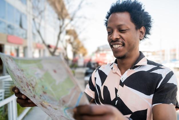 Retrato de homem afro-turista procurando direções no mapa enquanto caminha ao ar livre na rua
