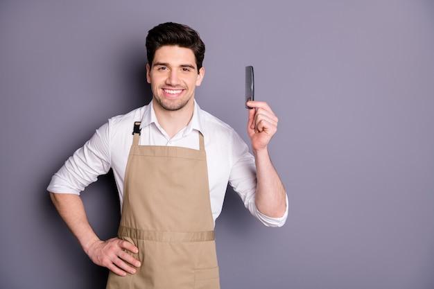 Retrato de homem alegre cabeleireiro segurando o pente pronto, penteado estiloso, usar camisa branca isolada sobre a parede de cor cinza