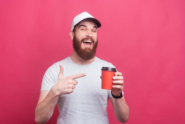 Retrato de homem alegre com barba, apontando para a xícara de café para ir