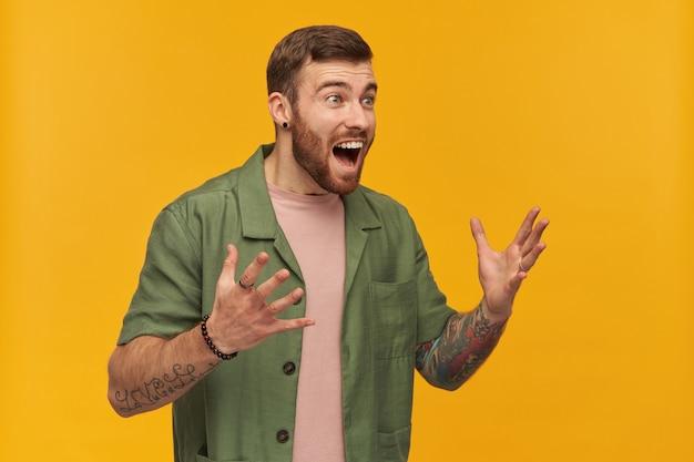 Retrato de homem alegre com barba e cabelo moreno. jaqueta verde de mangas curtas. levanta os braços de empolgação. tem tatuagem. observando à direita no espaço da cópia, isolado sobre a parede amarela