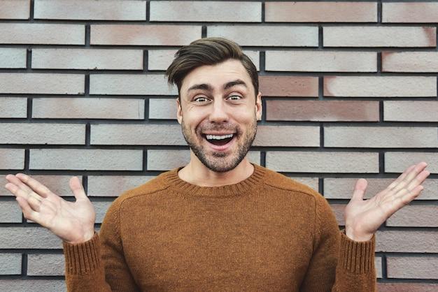 Retrato de homem alegre em retrato de estilo de vida de fundo de parede de tijolo de cidade urbana. conceito de carreira e empreendedorismo.