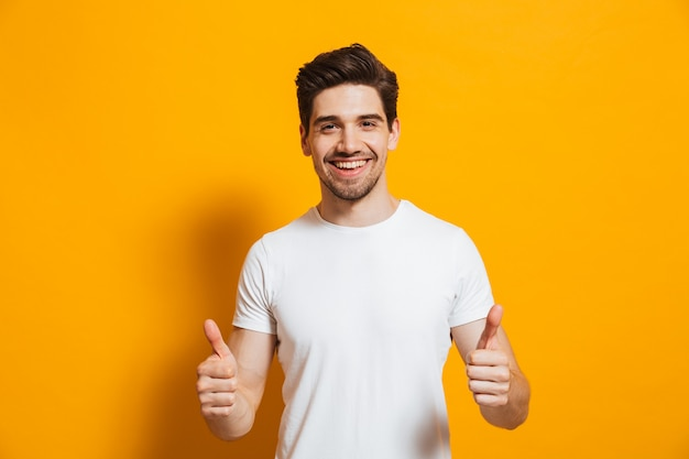 Retrato de homem alegre em roupas básicas, sorrindo e mostrando os polegares para a câmera