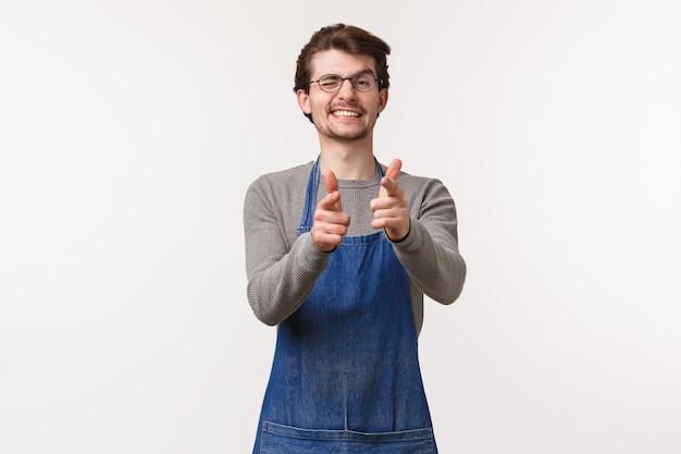 Retrato de homem amigável alegre no avental, trabalho na cafeteria ou restaurante, mostrar sinal de saudação informal pistolas de dedo apontando e piscadela, convidando para visitar sua loja, parede branca