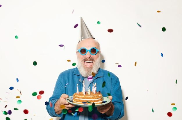 Retrato de homem animado sênior em óculos de sol, sorrindo para a câmera enquanto está sob o confete e segurando um bolo isolado no fundo branco