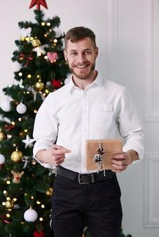 Retrato de homem apontando um presente