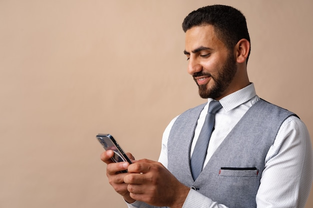 Retrato de homem árabe usando seu smartphone em estúdio