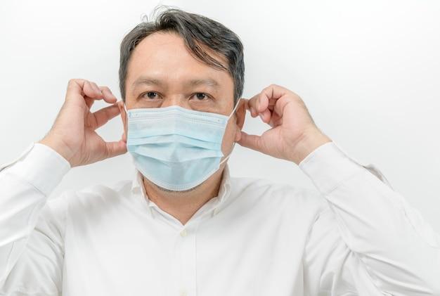 Retrato de homem asiático de camisa branca e máscara médica facial para proteção contra vírus