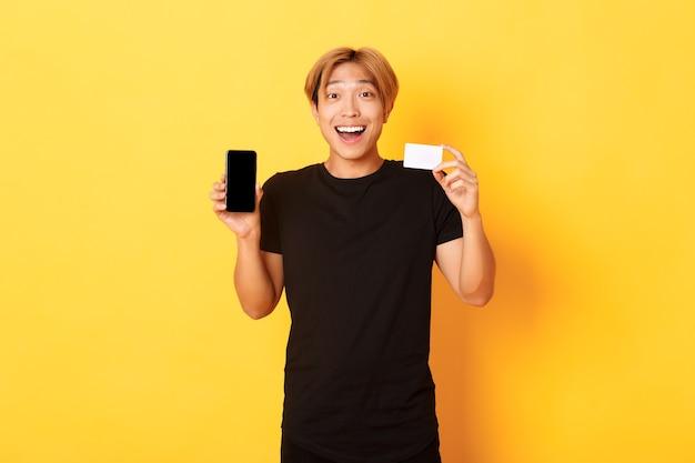 Retrato de homem asiático feliz animado, mostrando a tela do celular e o cartão de crédito com um sorriso alegre, em pé na parede amarela