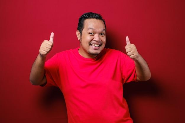 Retrato de homem asiático feliz mostrando os polegares para cima, fazendo gesto de aprovação com os dedos e ambas as mãos, sorrindo, mostrando que ele é bom, isolado sobre o fundo vermelho do estúdio