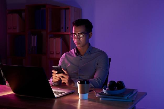 Retrato de homem asiático que texting no quarto escuro sentado no laptop